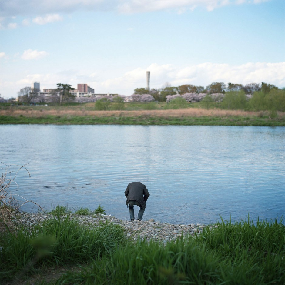 a man looking down the tama river, march 2014.
